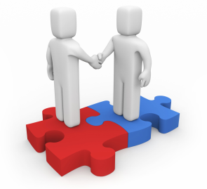 Two figures shaking hands on top of two puzzle pieces fit together