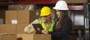 Two employees in a warehouse consulting a tablet