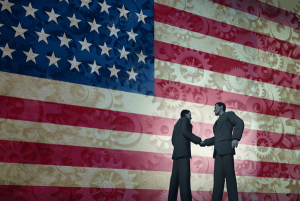 American flag with business people shaking hands