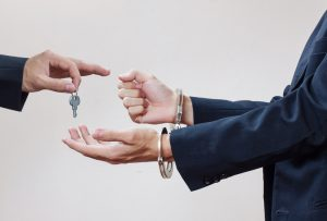 Photograph of a man in handcuffs and someone else handing him the keys.